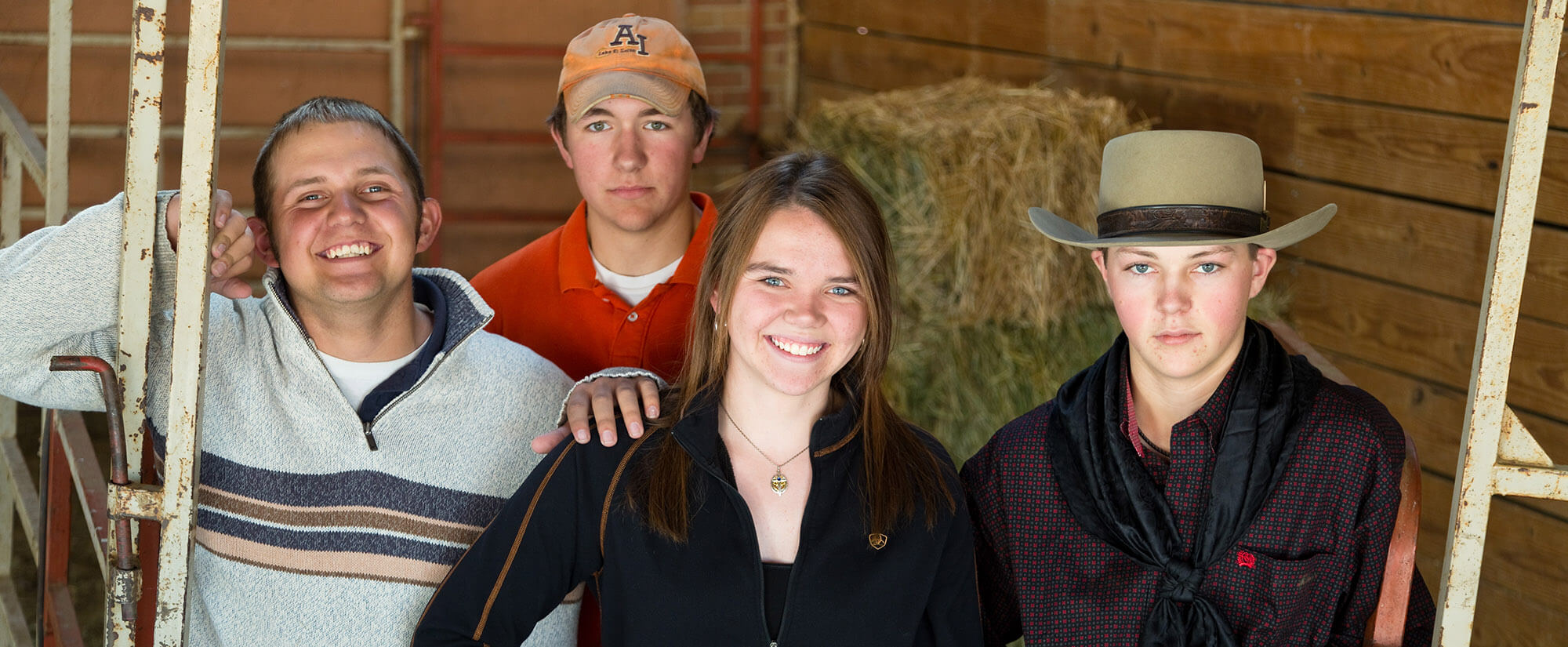 Four young students looking toward the camera, standing in a barn.
