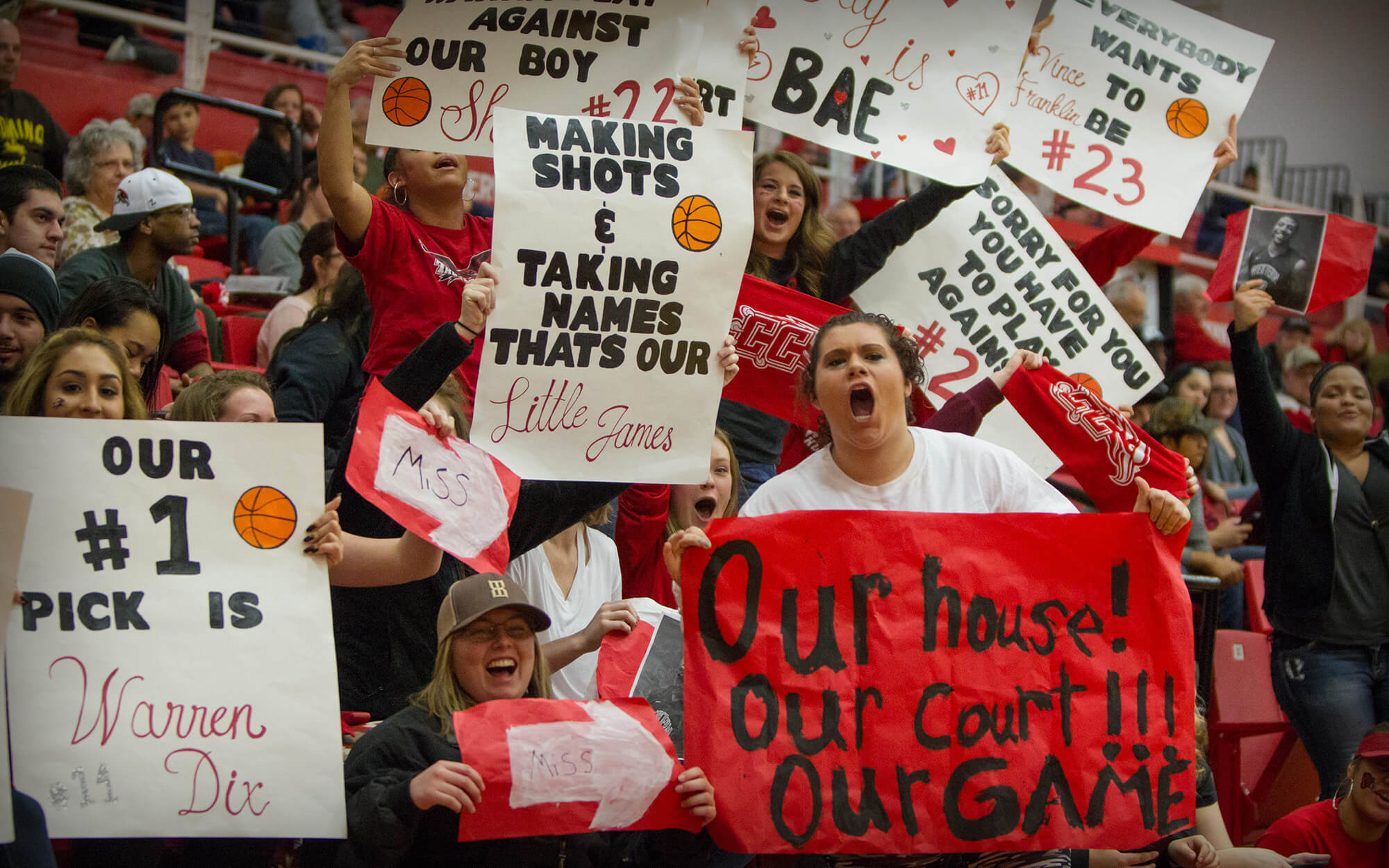 Students with homemade signs to cheer on basketball players.
