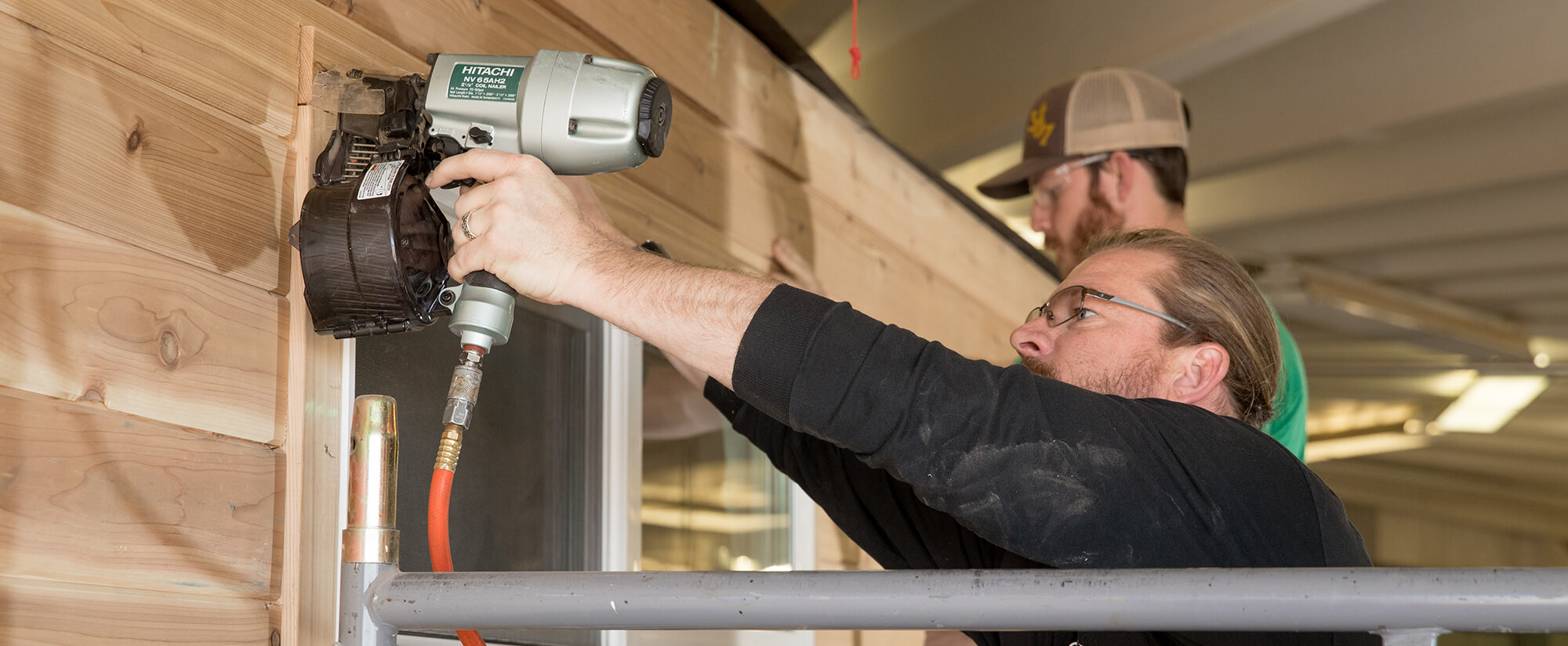 A student uses a nail gun to frame a window of a tiny home.