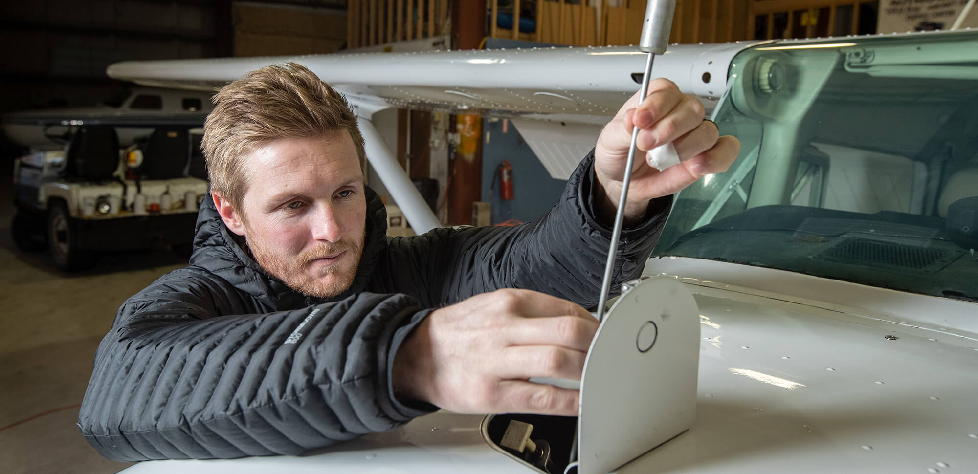 Certified flight instructor Brek Carper checks the oil of a plane at Natrona County International Airport.