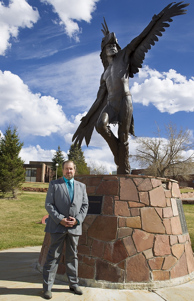 Casper College President Dr. Darren Divine in front of the Heyoka statue on campus