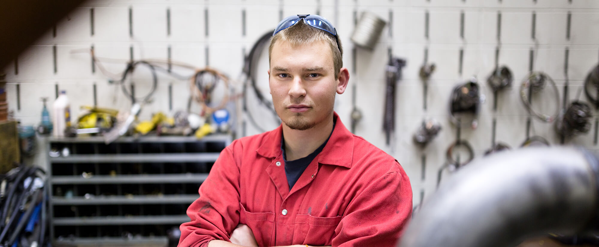 Casper College student poses in a workspace with diesel tools.