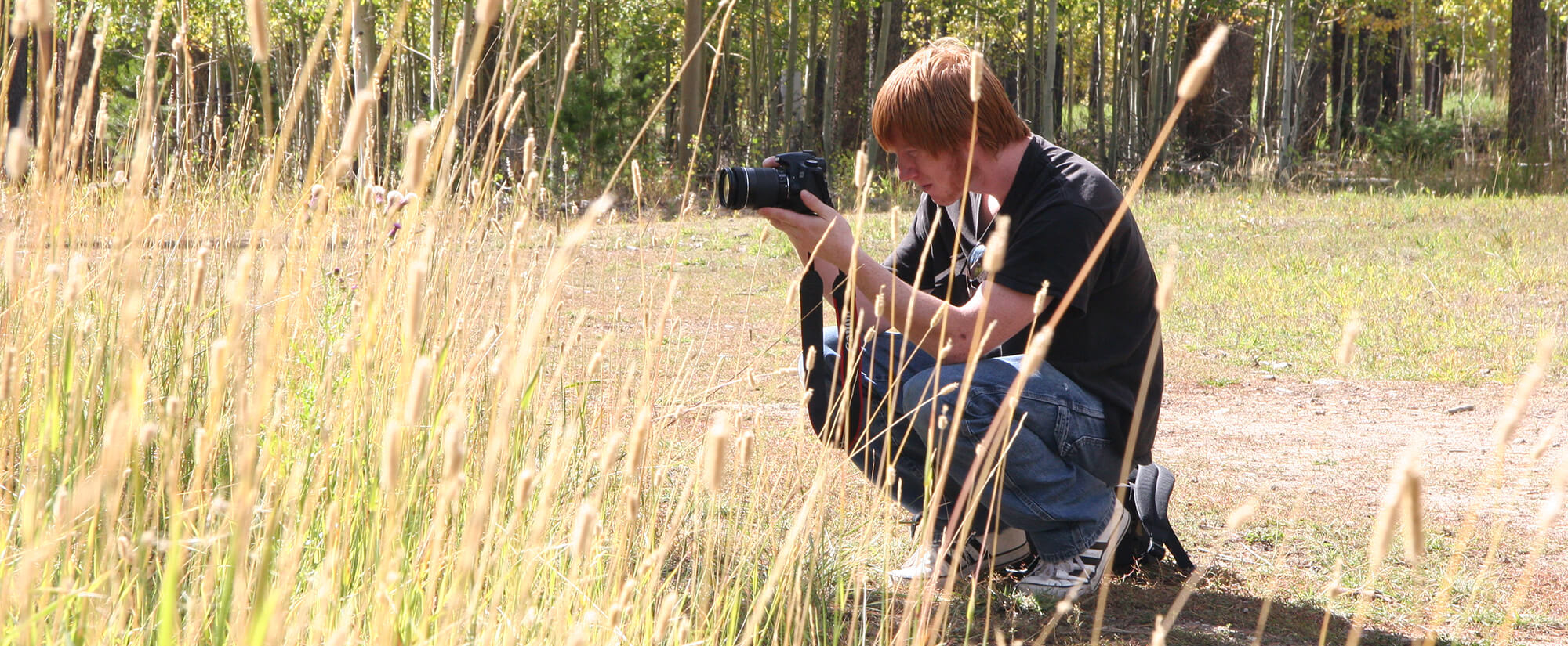 Student holding a DSLR camera crouched in tall grass on top of a mountain.