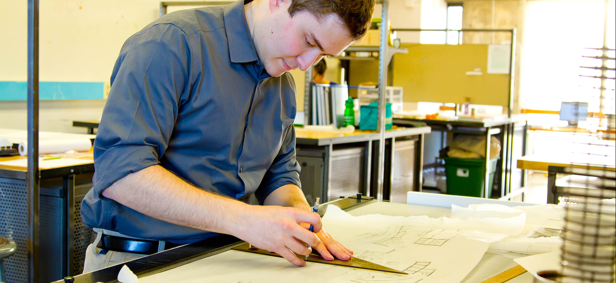 Photo of a young man working on construction plans in a workshop.