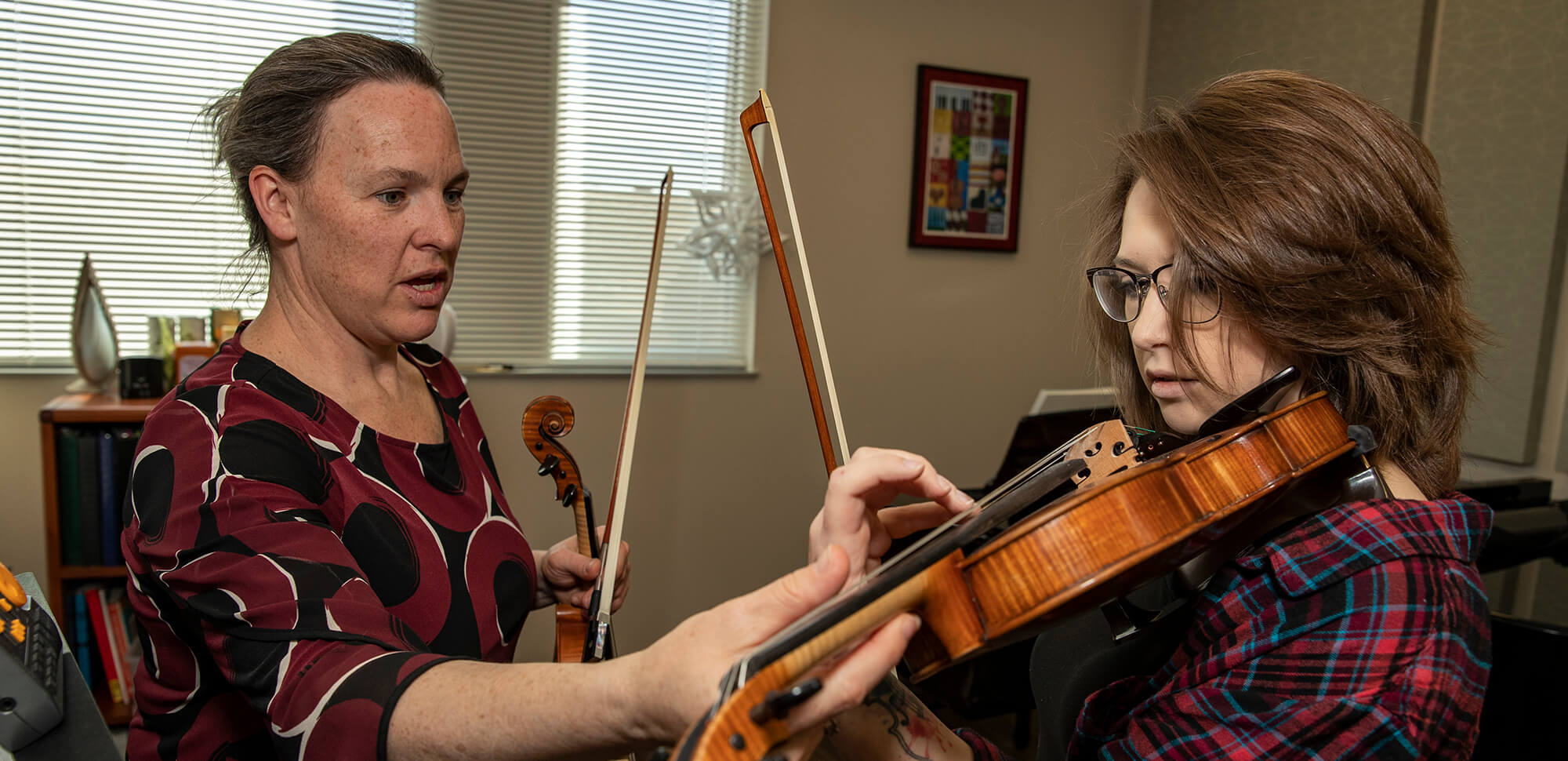 Casper College instructor gently adjust the handgrip of a student playing the violin.
