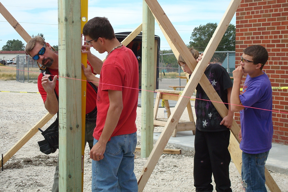 Photo of Rob Hill working with Transitions students on a post placing for a redwood and cedar pergola.