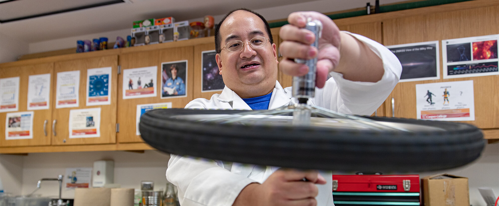 Instructor demonstrates physics related to a bicycle wheel.