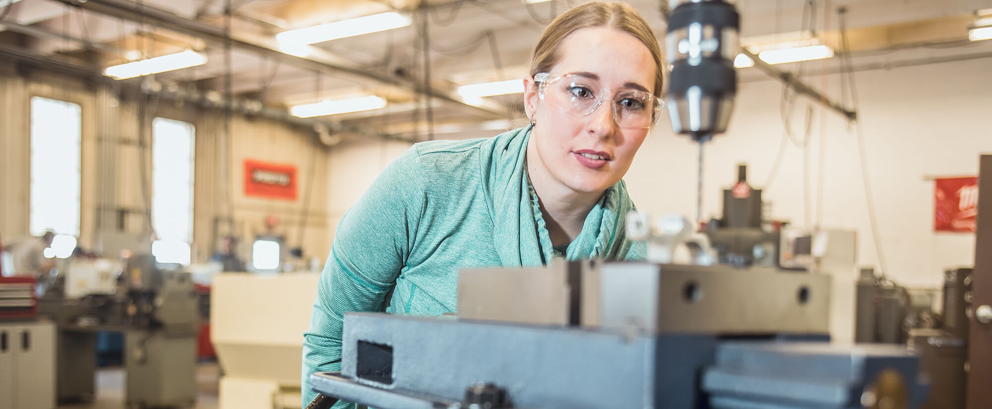 A female student wearing safety glasses in a machine tool classroom.