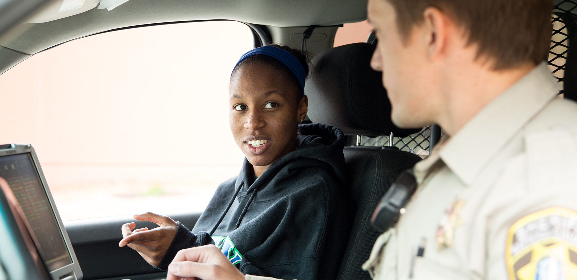 A female student doing a ride-along with a police officer.
