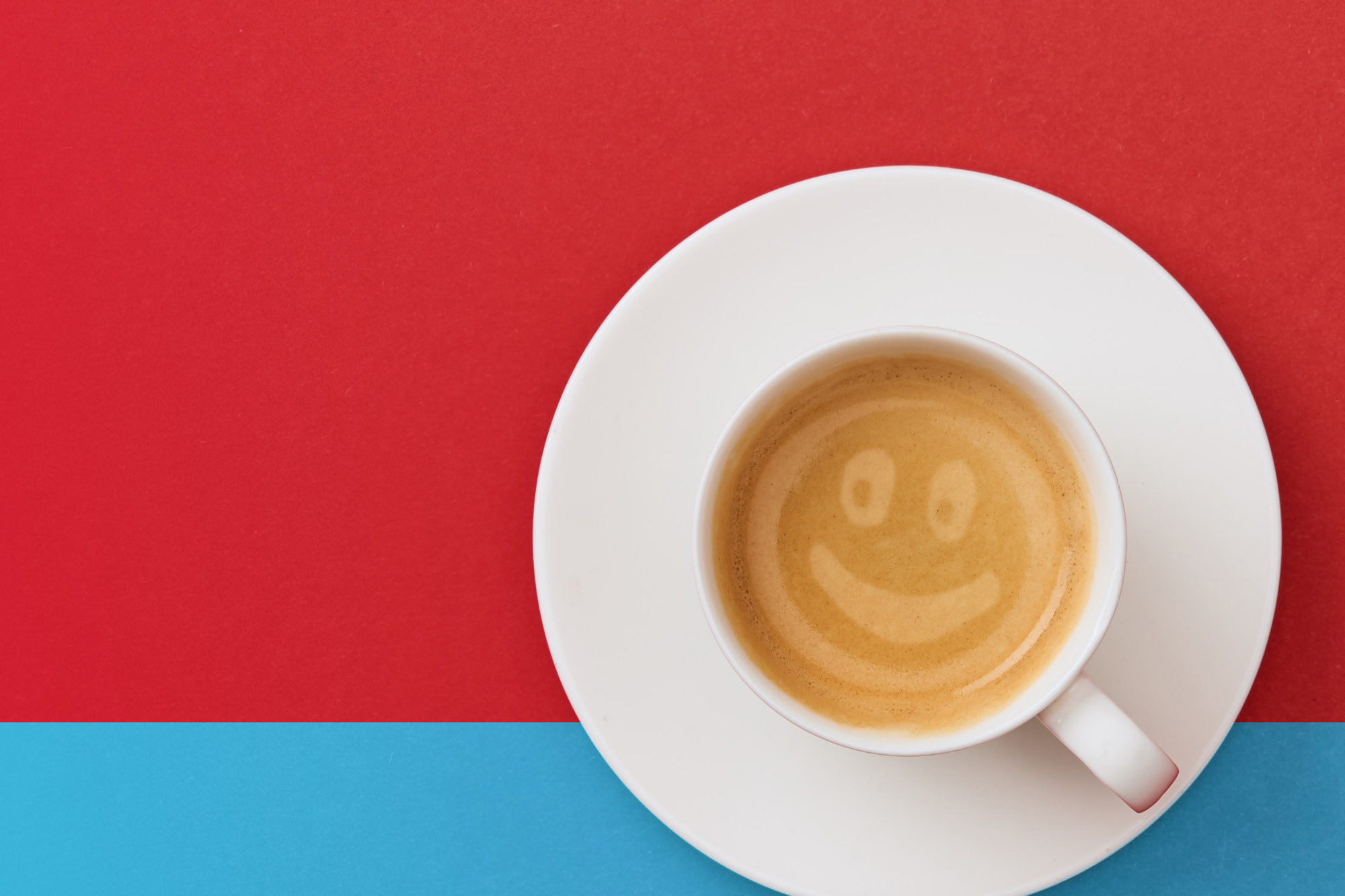 Photo of a white coffee cup that holds a coffee drink with a smiley face in the foam on a red and turquoise background