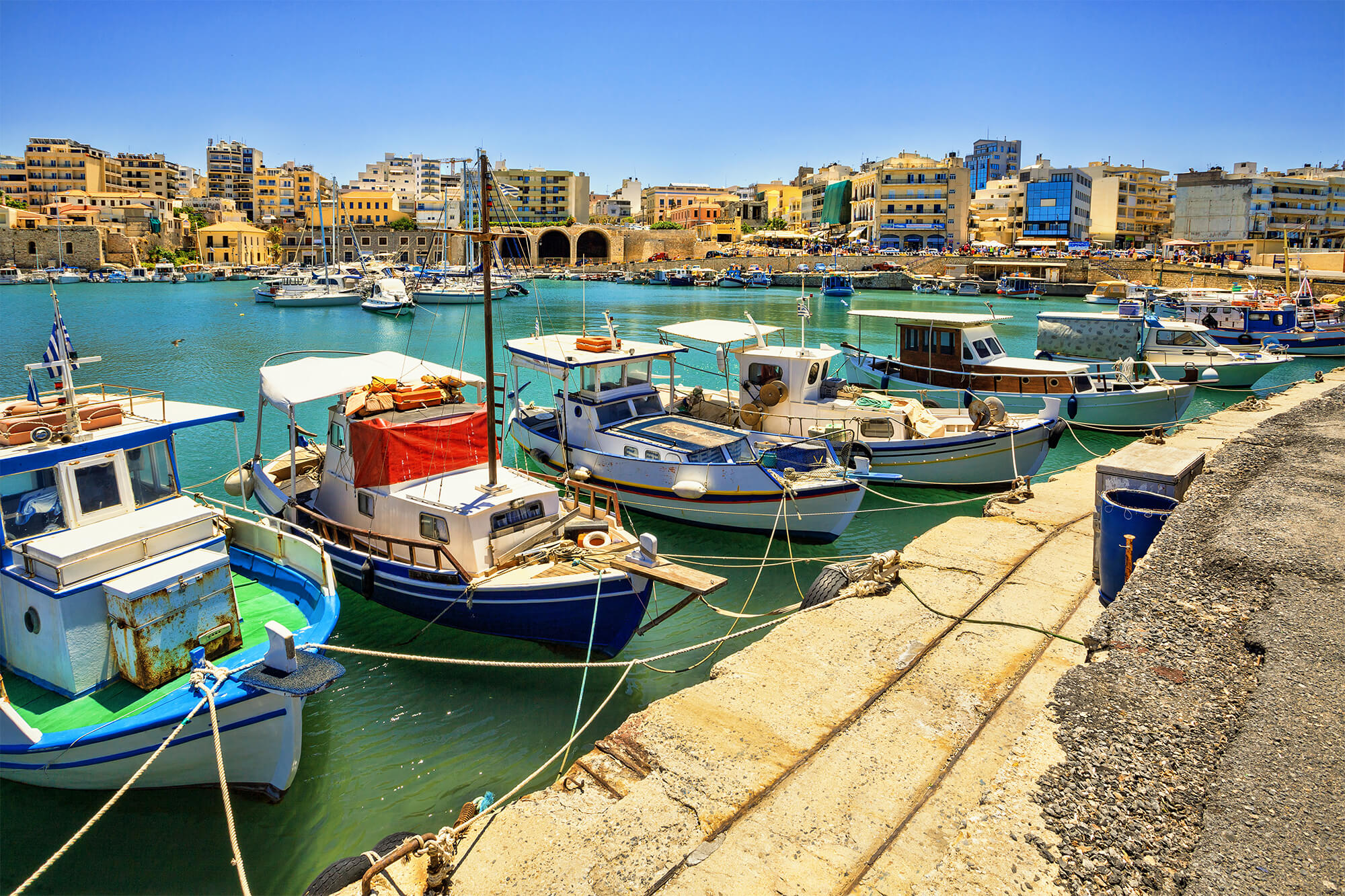 Color photo of boats docked in a port on the Greek island of Crete
