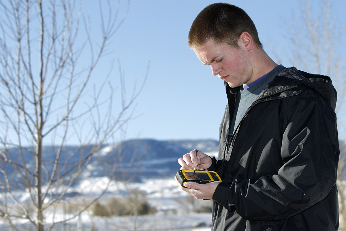 Photo of male student using a GIS device.