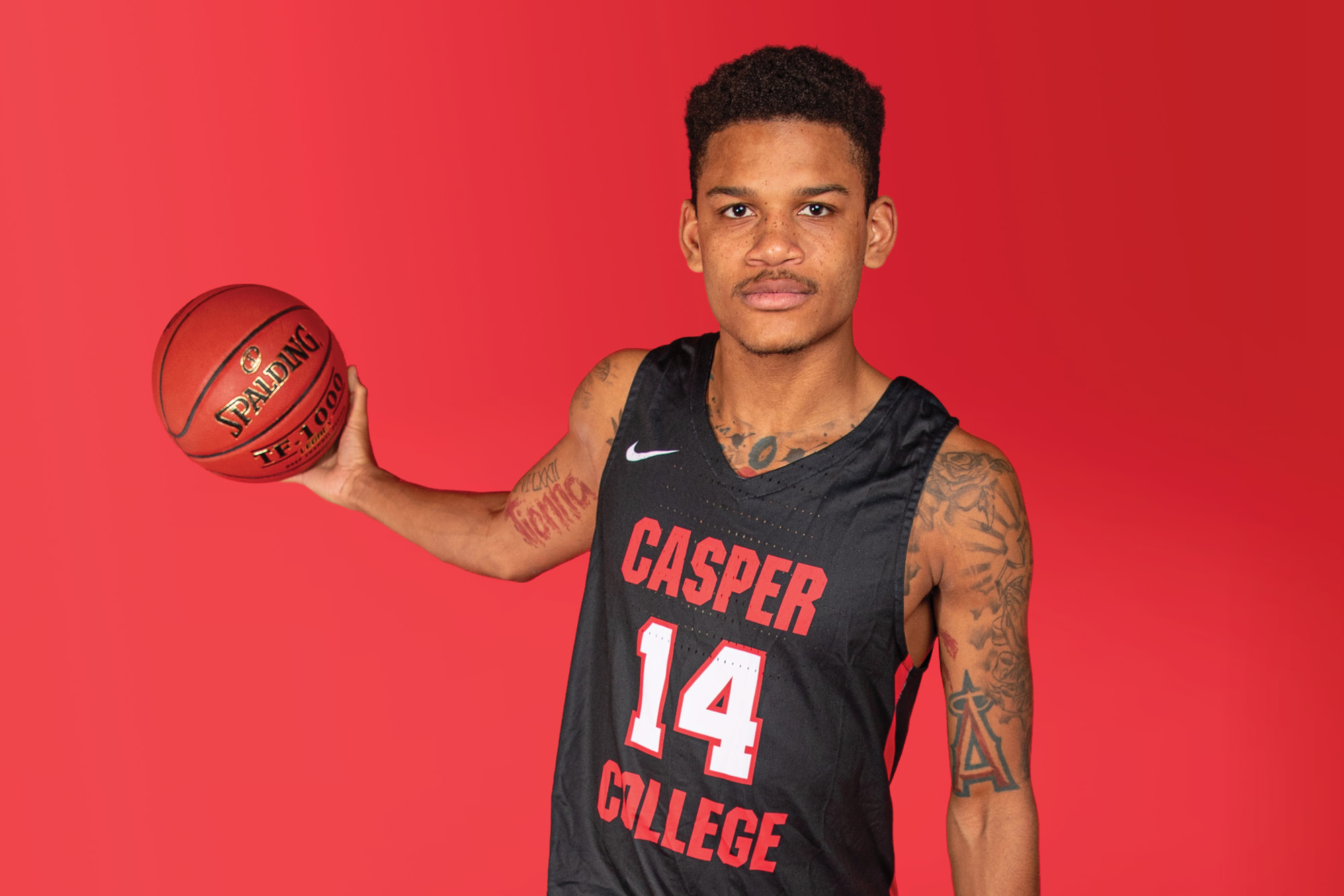 Casper College basketball player Tavion Robinson holding a basketball.