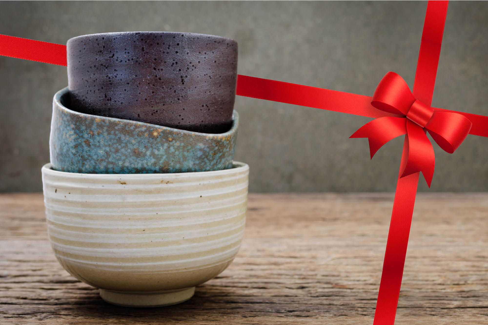 Photo of ceramic bowls with a red bow in the background.