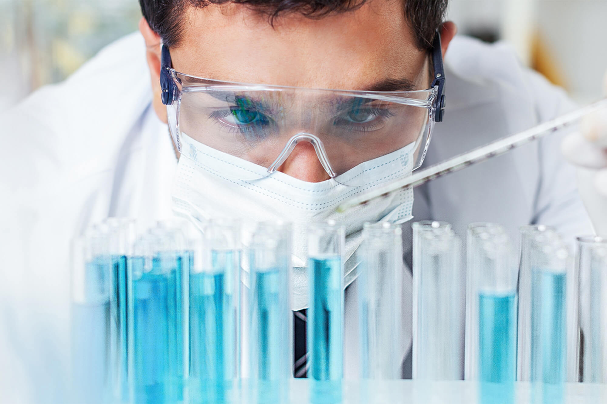 Photo of man with safety glasses and face mask with test tubes filled with blue liquid.
