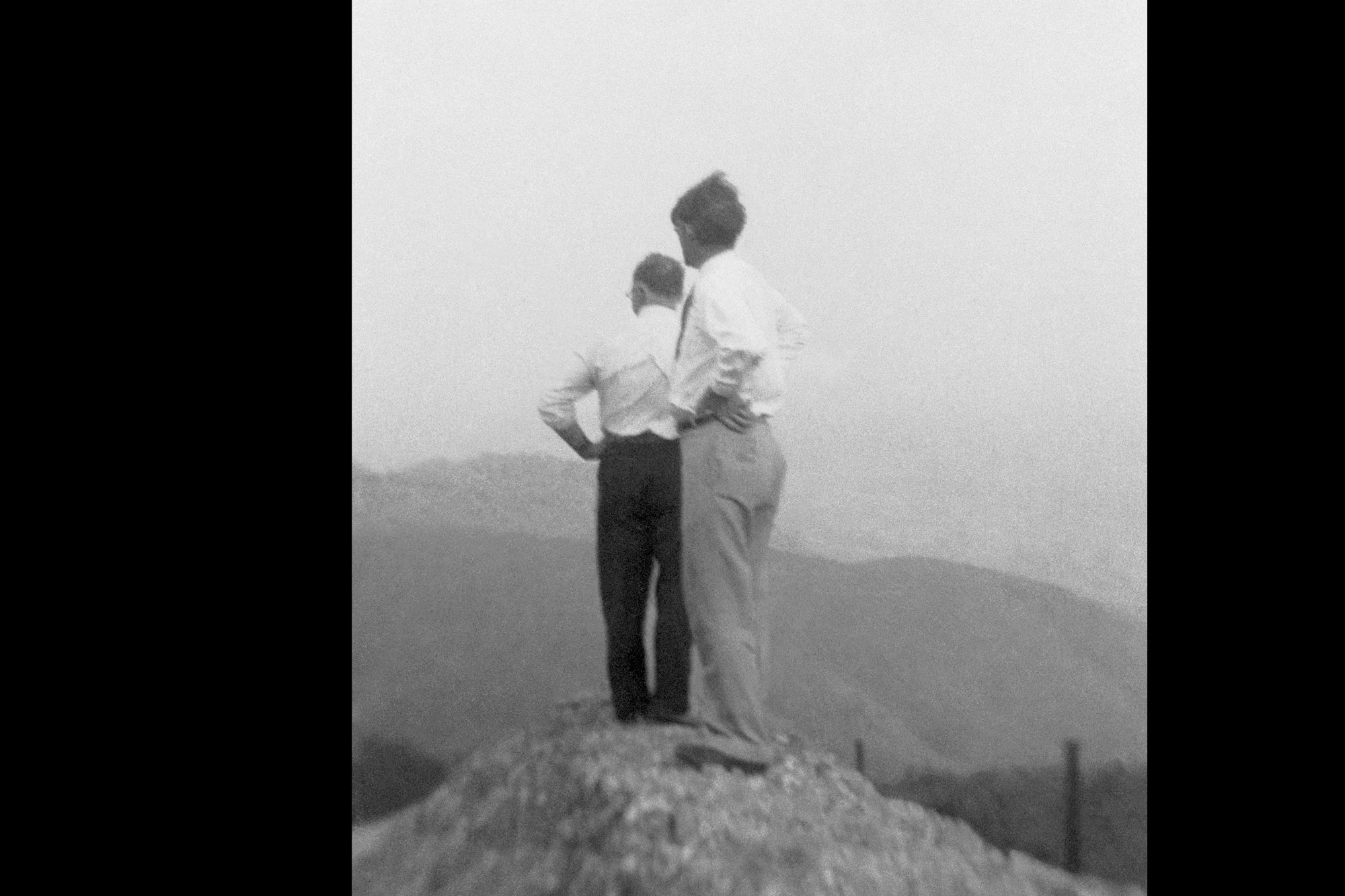 Photograph of two unidentified men looking into the distance.