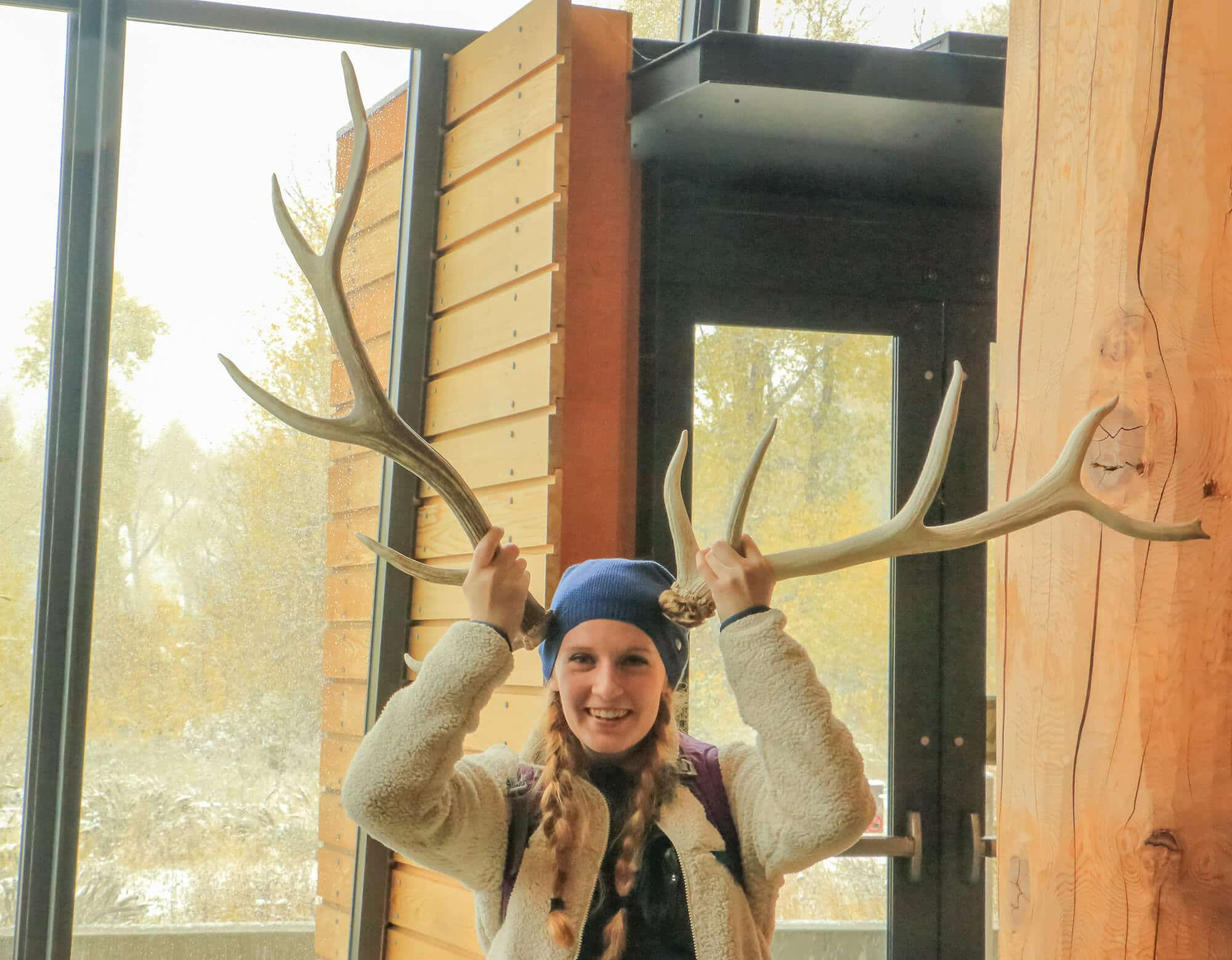 Student goofing off and holding antler and horn to her head