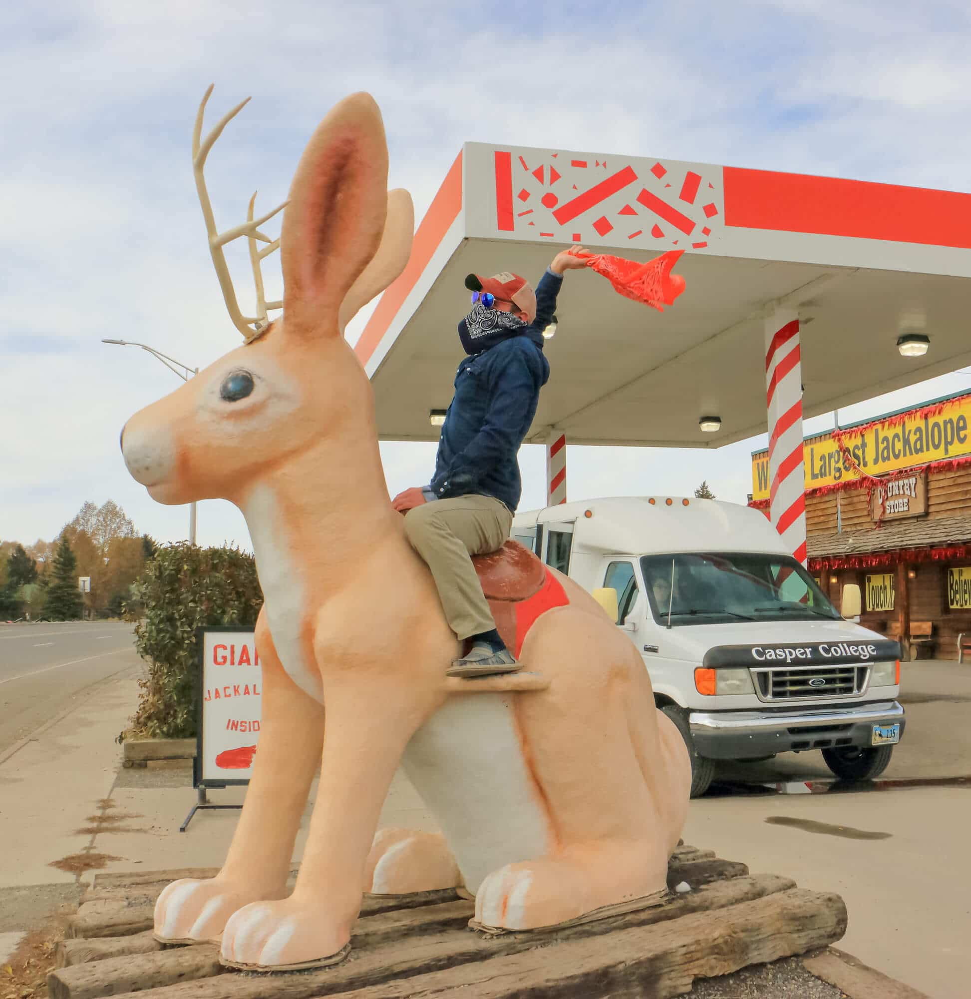 Student having fun posing on a statue of a jackalope