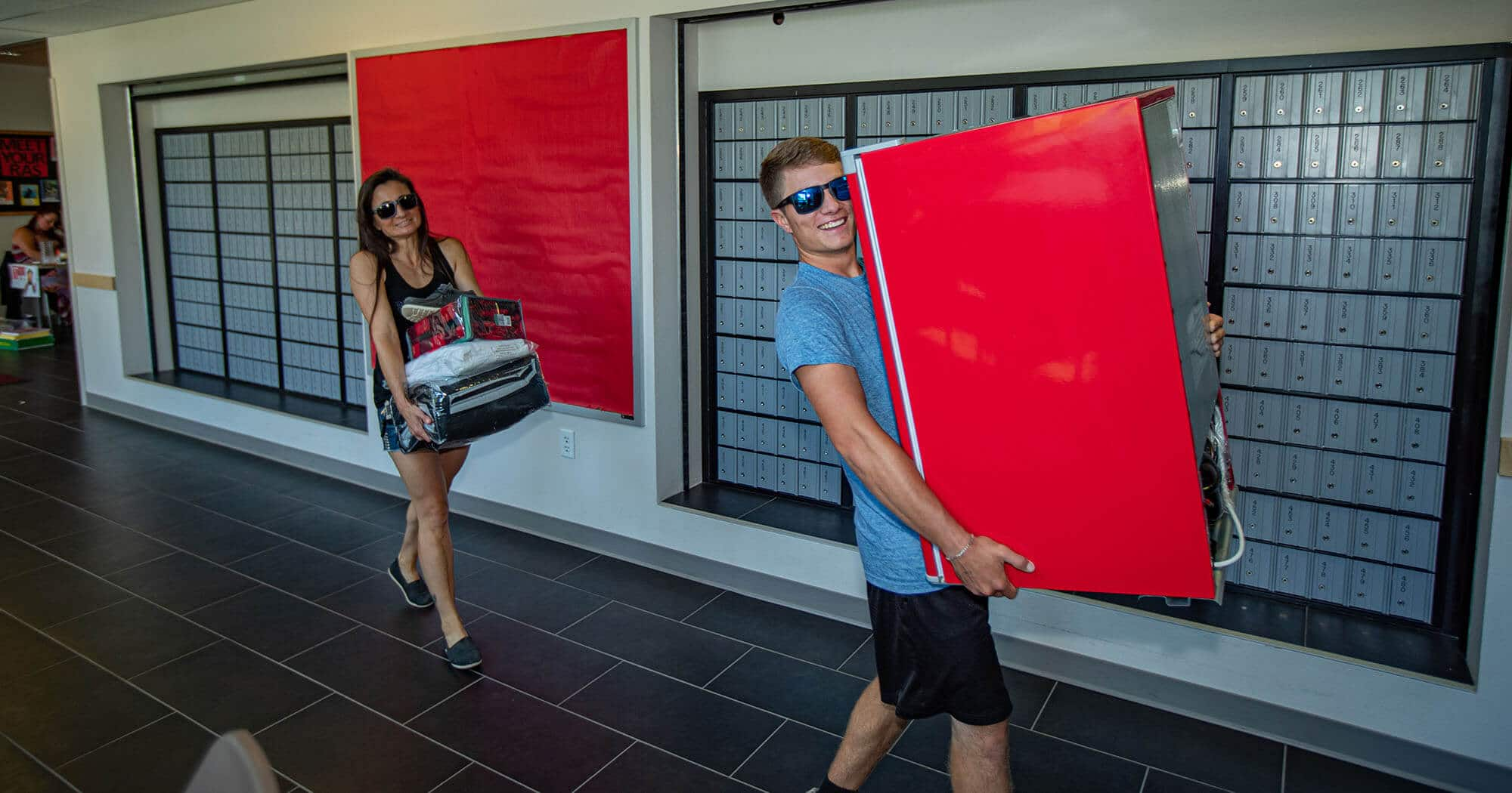 A student carrying a mini-fridge is followed by his mother carrying bedding for his dorm room.