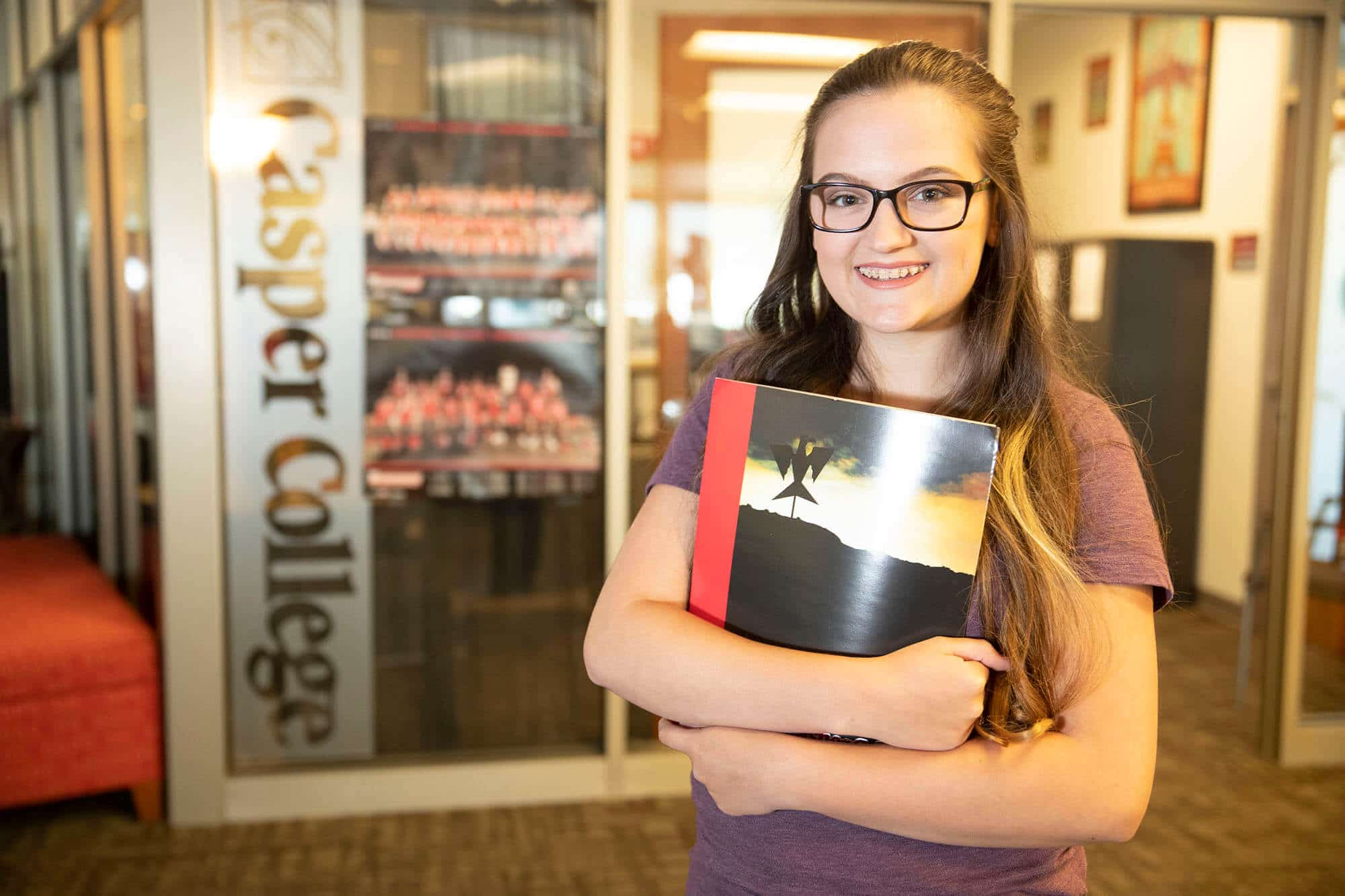 Female student smiling and holding a folder with an office behind her that says Casper College on the window