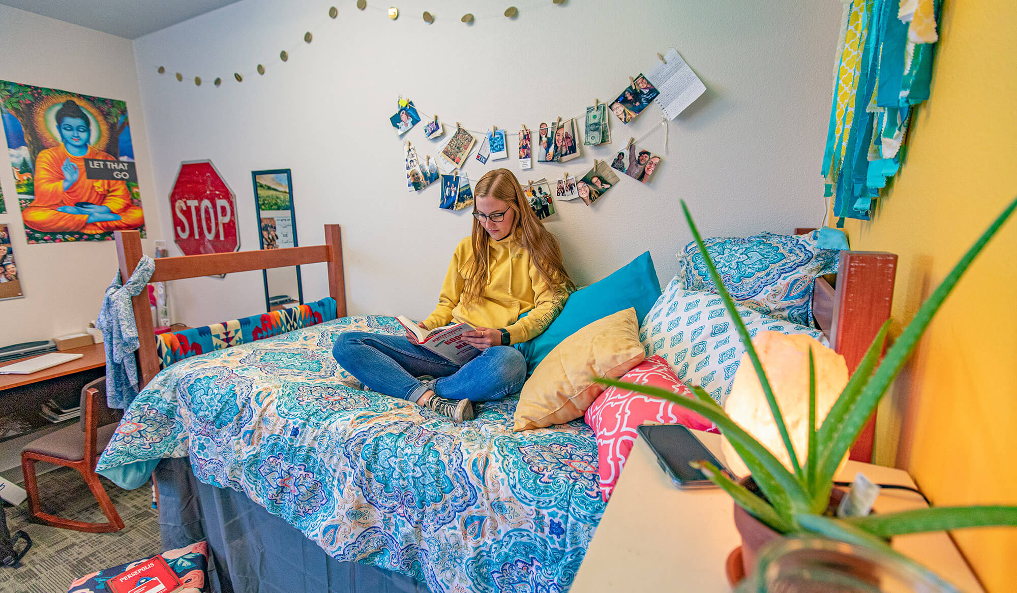 A student reading a book while sitting on the bed of her dorm room; her desk is in the background.