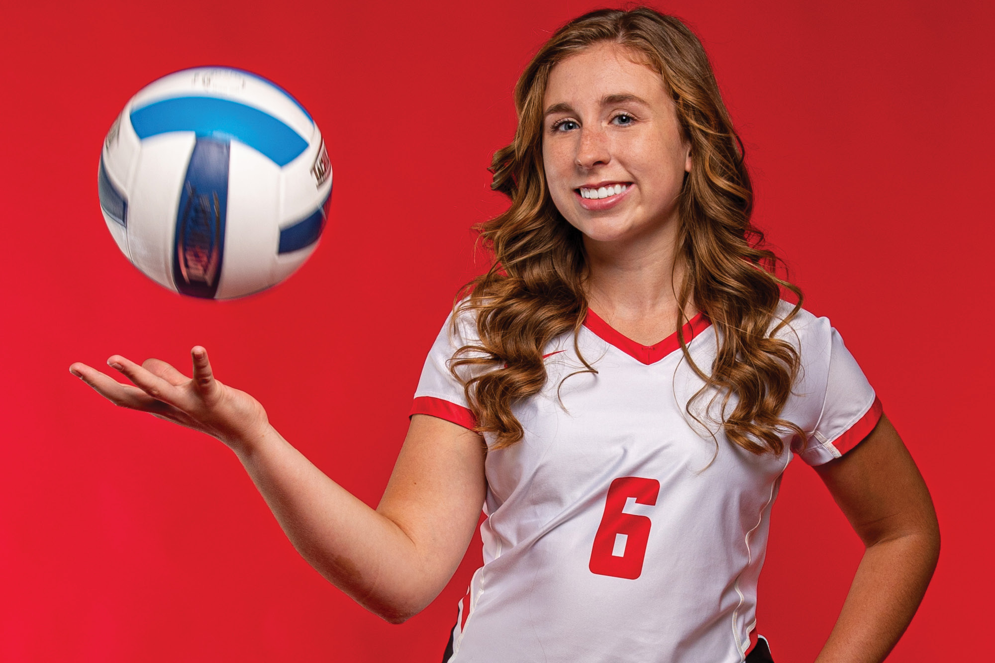Photo of Casper College volleyball player Kylie Watson tossing up a volleyball