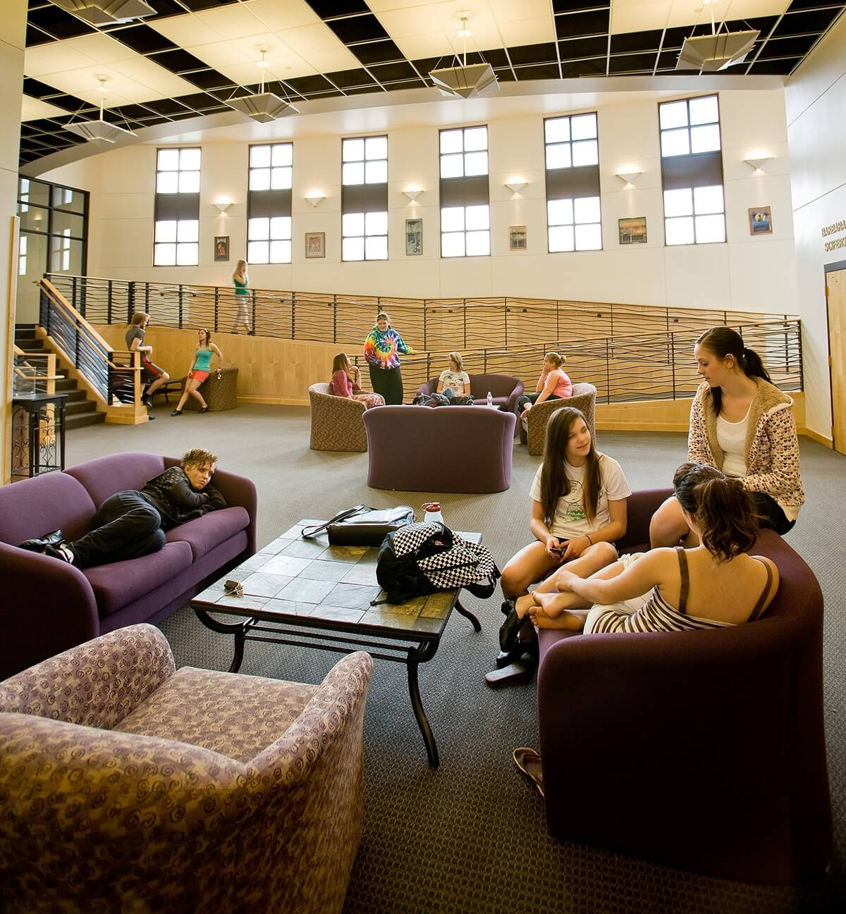 Photo of students in different study areas in a large sun-lit common space in the Krampert Complex